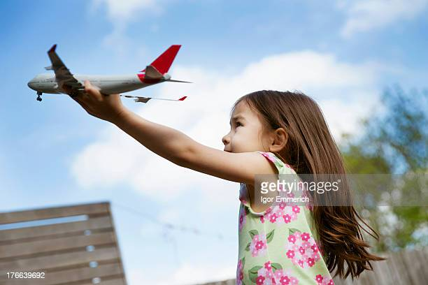 Young girl in garden playing with toy airplane