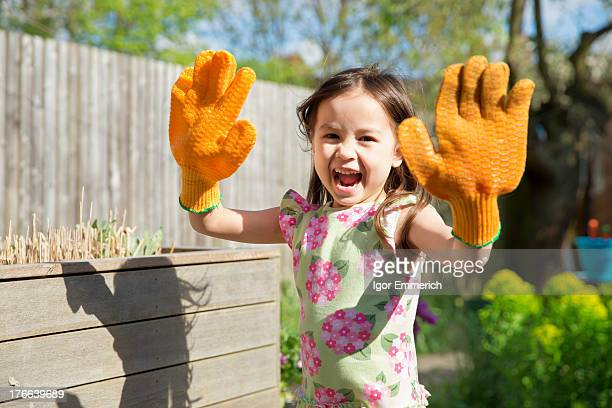 Young girl in garden wearing oversized gloves