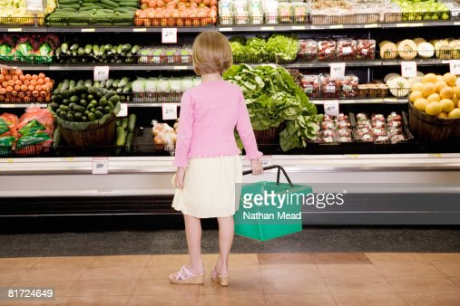 Young girl in grocery store produce aisle with shopping basket : Stock Photo