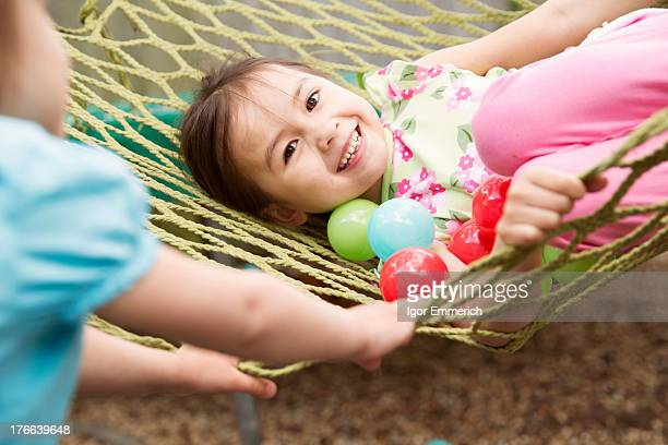 Young girl in hammock with colored balls