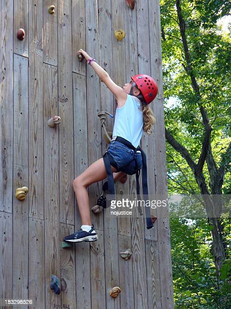 Young girl in helmet climbing a wooden wall with footholds