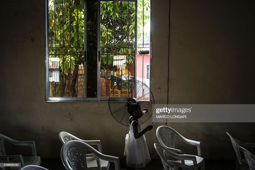 A young girl in her Sunday's best plays in the church after the service at the Winners Chapel International in the Weasay district of Monrovia on May 1, 2016. / AFP / MARCO