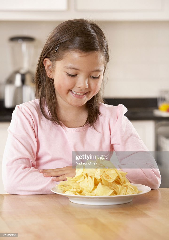 Young girl in kitchen looking at a plate of potato chips smiling : Stockfoto