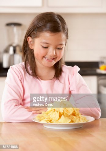Young girl in kitchen looking at a plate of potato chips smiling : ストックフォト