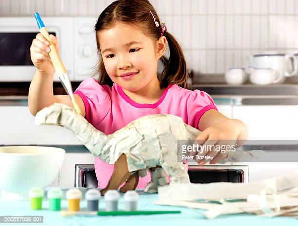 Young girl (6-7) in kitchen, making paper dinosaur, smiling