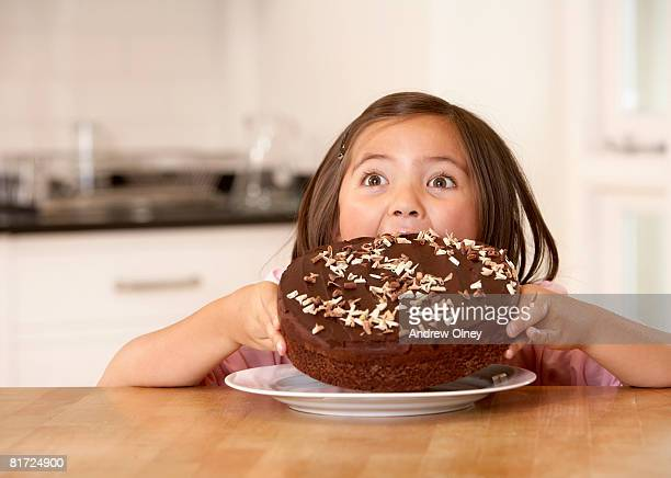 Young girl in kitchen trying to eat an entire cake all at once