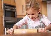 Young girl in kitchen using rolling pin and smiling