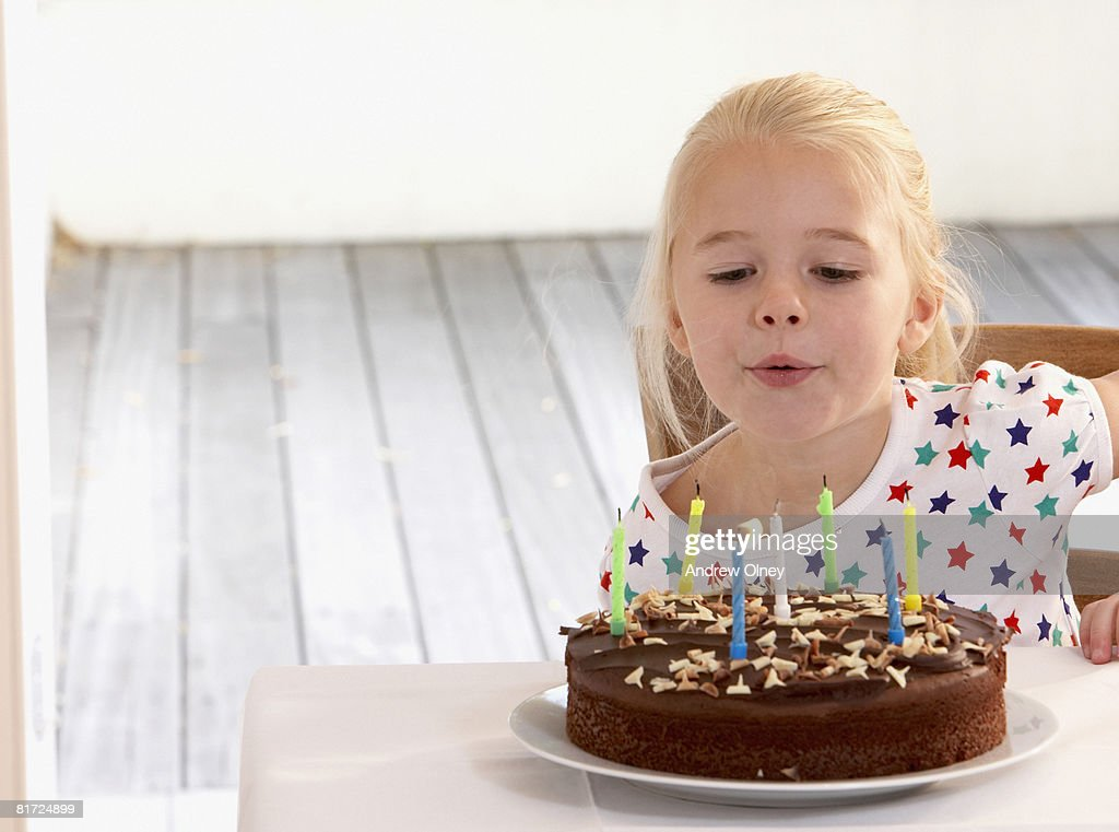 Young girl in kitchen with birthday cake blowing out candles : Stock Photo
