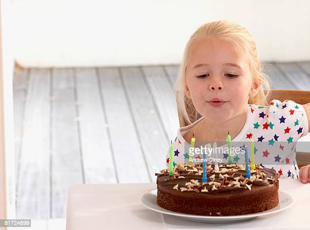 Young girl in kitchen with birthday cake blowing out candles