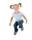 Adorable young girl leaping in the air, it sends her pigtails on a gravity defying ride. Studio shot, isolated on white. Some motion blur in legs (because of the action nature of the picture) but her