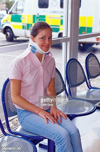 Young girl in neck brace sitting in hospital waiting area