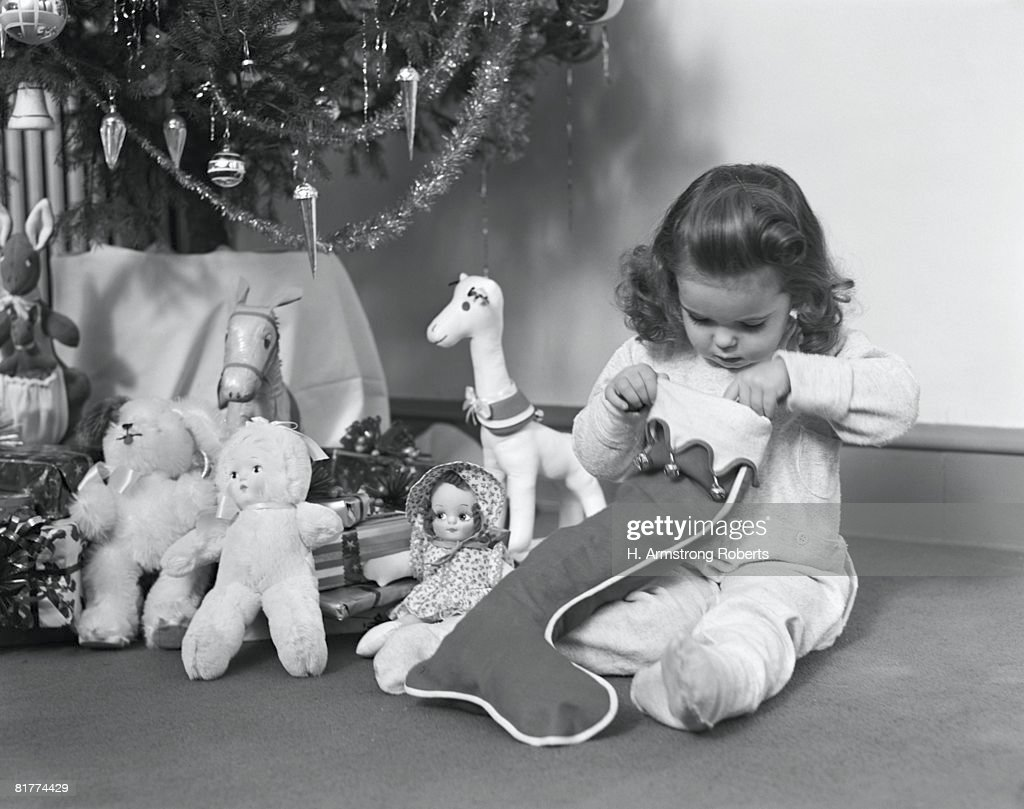 Young girl in pajamas, opening Christmas stocking next to Christmas tree. (Photo by H. Armstrong Roberts/Retrofile/Getty Images) : Stock Photo