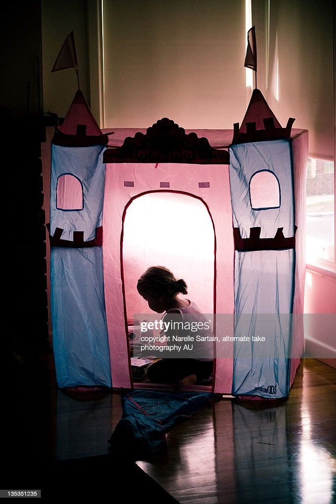 Young girl in pink and blue tent : Stock Photo