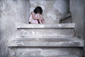 little girl sits lonely on cold stairs