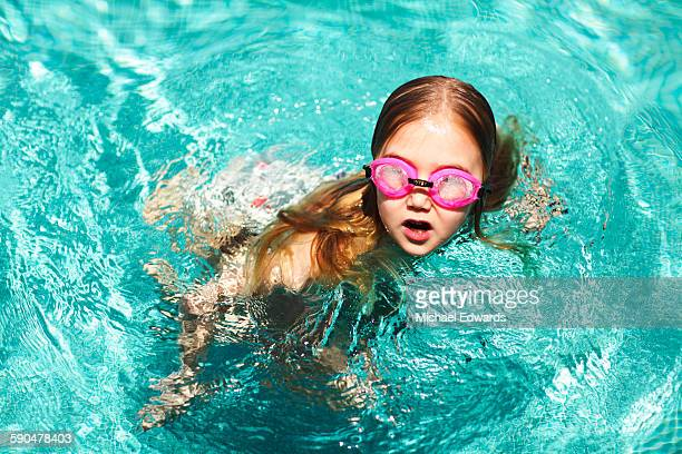 young girl in pool with pink goggles