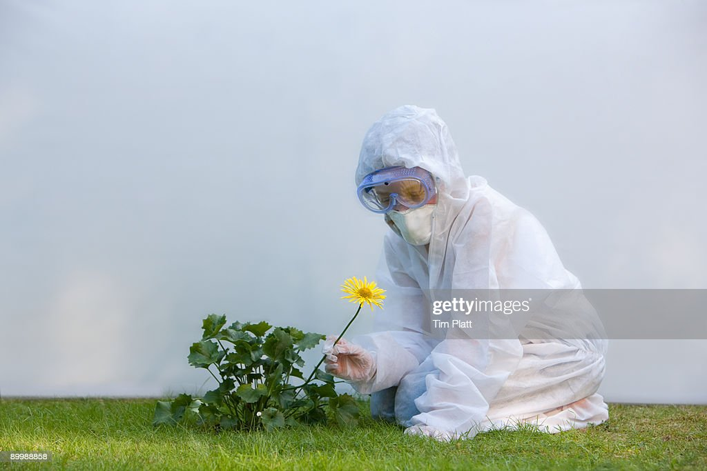 Young girl in protective clothing with flower. : Stock Photo
