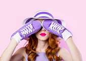 Young girl in purple clothes with shoes on pink background