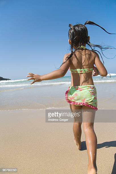 Young girl in swimsuit running on beach