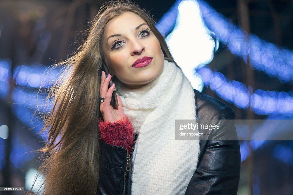 Young girl in the city at night using smart phone : Stock Photo