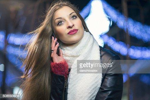Chica joven en la ciudad por la noche usando teléfono inteligente : Foto de stock