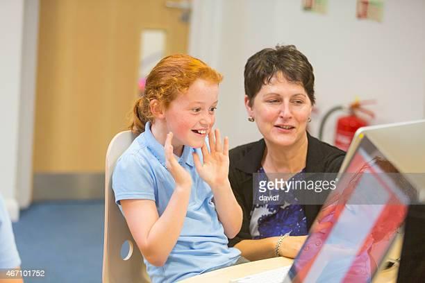 Jeune fille dans la salle de class'avec un ordinateur