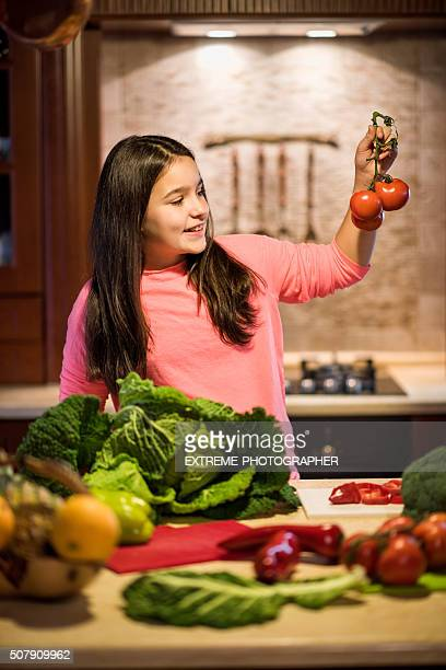 Young girl in the kitchen looking at tomatoes