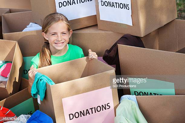 Young girl in the middle of many donation boxes