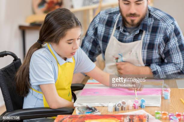 Young girl in wheelchair in art class