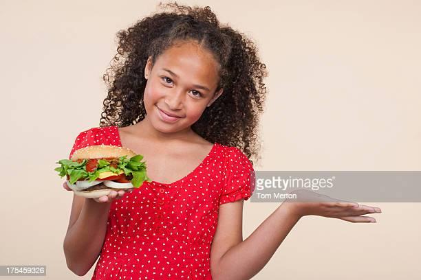 Junges Mädchen im Innenbereich hält einen hamburger