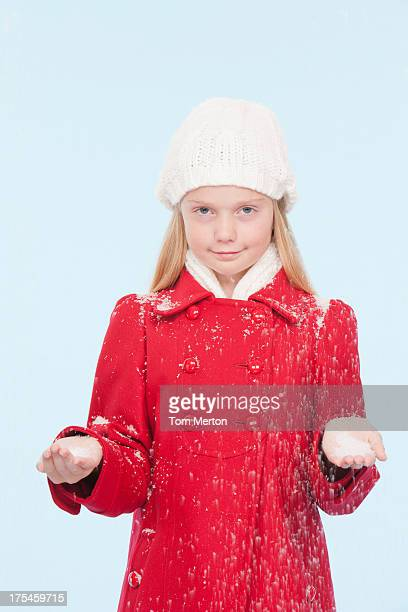 Young girl indoors holding snow in hands