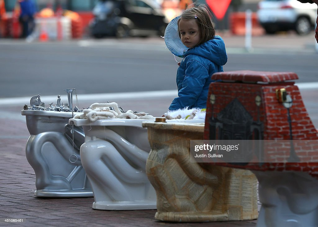 A young girl inspects decorated toilets that is part of a public art installation titled 'C'mon, give a shit' to mark World Toilet Day and to bring attention to a project to convert retired MUNI buses into mobile showers for the homeless on November 21, 2013 in San Francisco, California. Lava Mae founder Doniece Sandoval coordinated the public art installation of decorated toilets to raise awareness about the millions of people around the world who do not have access to clean and private toilets. The installation also promotes the nonprofit Lava Mae's project to convert old San Francisco municipal buses into mobile showers for homeless people in the city.