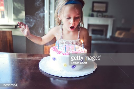 Young Girl is Blowing Out Candles on Birthday Cake