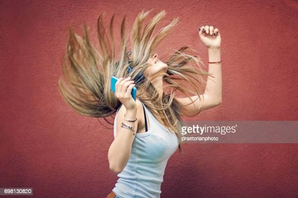 Jeune fille est danse et écoute la musique