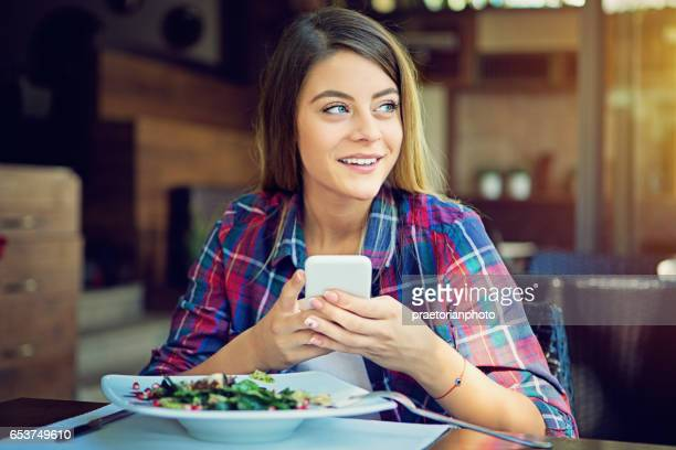 Young girl is eating salad in the restaurant and texting