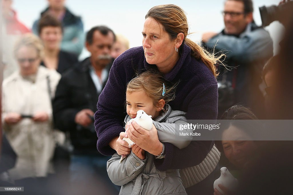 A young girl is helped as she prepares to release a white dove at a memorial ceremony at Dolphin Point in Coogee in on October 12, 2012 in Sydney, Australia. The ceremony marks tenth anniversary of the 2002 Bali suicide bombs that killed 202 people including 88 Australians.