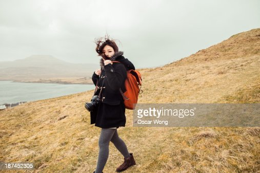 A young girl is hiking alone in the wind : Stock Photo