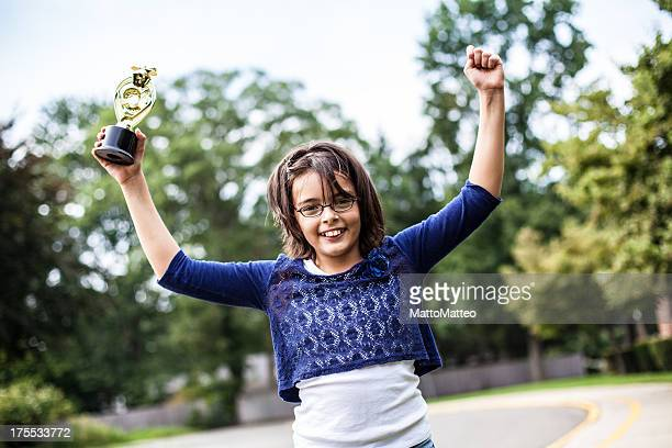 Young girl is holding a trophy