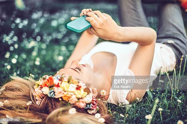 Junges Mädchen ist in der Wiese liegen und nimmt selfies