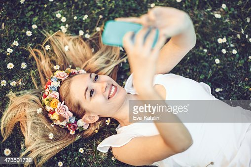 Young girl is lying in the grass and taking selfies