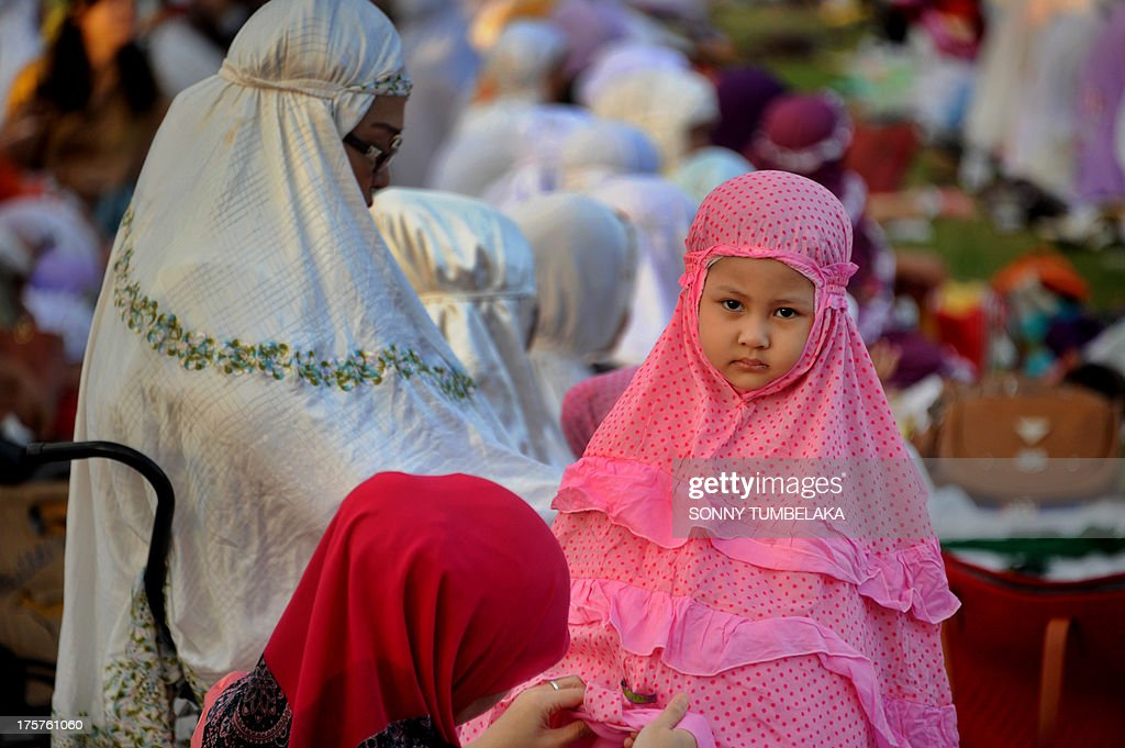 A young girl is pictured as Indonesian Muslims take part in special morning prayers near the Bajrah Sandhi monument in Denpasar on Indonesia's island of Bali on August 8, 2013. Muslims around the world will celebrate Eid al-Fitr this week, marking the end of holiest month of Ramadan during which followers are required to abstain from food, drink and sex from dawn to dusk.