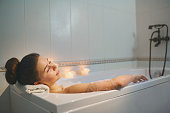 Young girl is resting in a bathtub with foam in bethroom with candles.