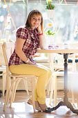A young girl is sitting in a cafe on the background of a large window. European woman with red hair is smiling. Vertical photo.