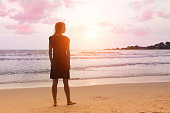 Fantasy scene: young girl is standing at sunset sea beach and dreaming or thinking about something. Woman is looking to horizon.