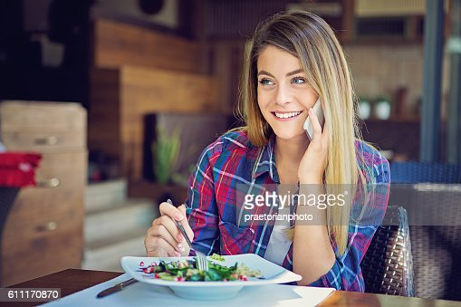 Young girl is talking using her mobile phone in restaurant : Stock Photo