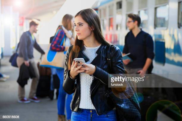 Young girl is texting while waiting for a train