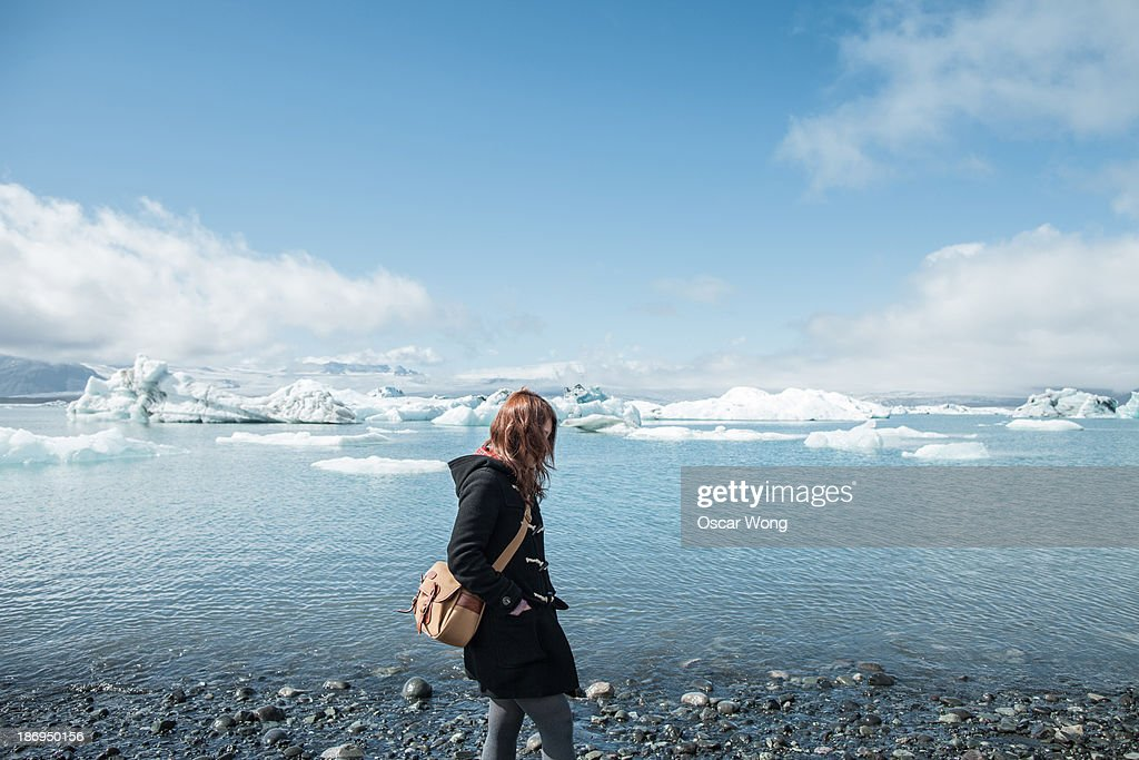 A young girl is walking by the glacier