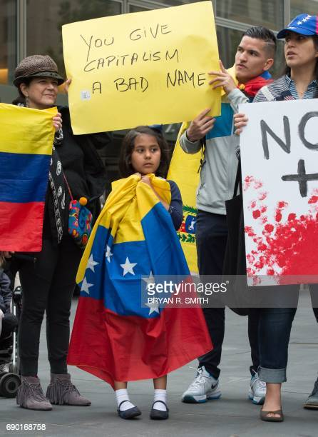 A young girl is wrapped in the Venezuelan flag while activists hold signs during a protest against Goldman Sach's bond purchase transaction of $28...