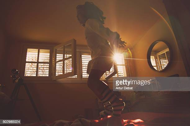 Young girl jumping and playing on the bed with beautiful sunrise light through the window.