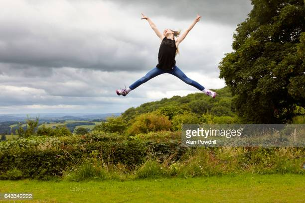 Young Girl Jumping For Joy In Green Landscape