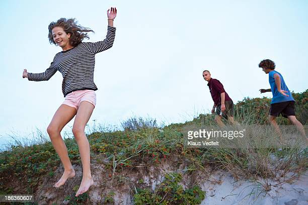 Young girl jumping fromsand dune